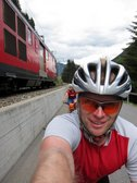 Emily and Cris are passed by a train while riding towards Oberalppass (Switzerland) resize