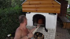 Ritchy puts food into the wood oven (Hungary) resize