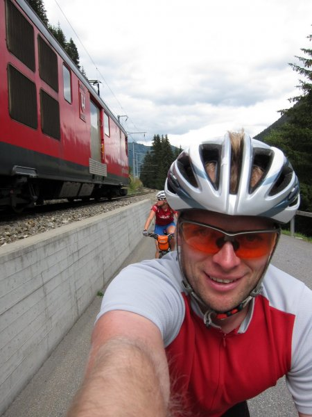 Emily and Cris are passed by a train while riding towards Oberalppass (Switzerland)