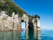 Georgia kayaking through the arch (Wainui Inlet)
