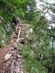 Cris climbs up through the cliffs (Slovenia)