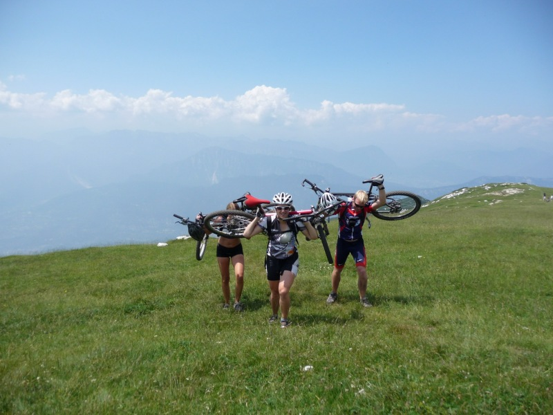 Frauke, Emily, and Cris carrying there bikes to the top of Monte Stivo (Lago di Garda, Italy)