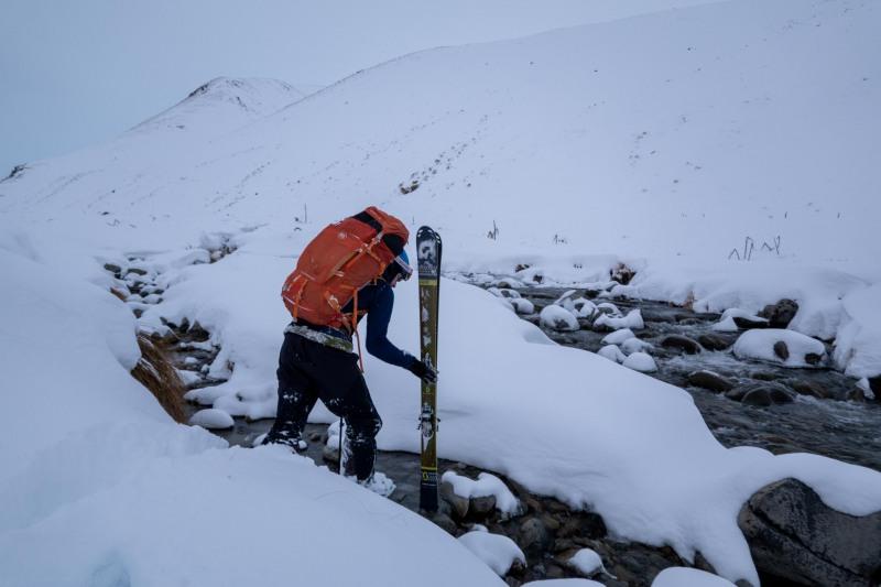 Craig crosses the river (Ski Touring Camp Stream Hut Aug 2021)