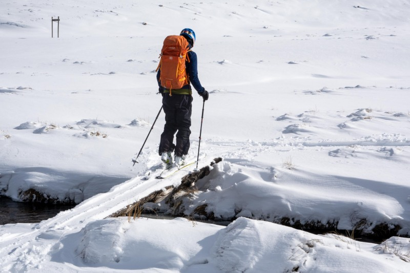 Craig crossing a little bridge (Ski touring Kirtle Burn Hut August 2021)