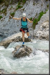 Leonie jumping across the river (Pirknerklamm Klettersteig)